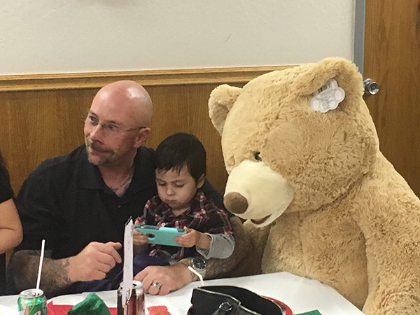 The Prize Bear looks on as the young guy racks up points of the Nintendo Switch.