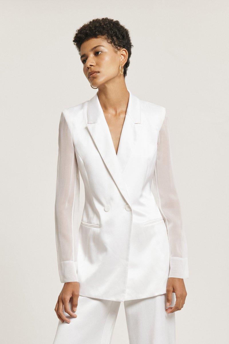 Black female model wearing a white blazer by Cushnie