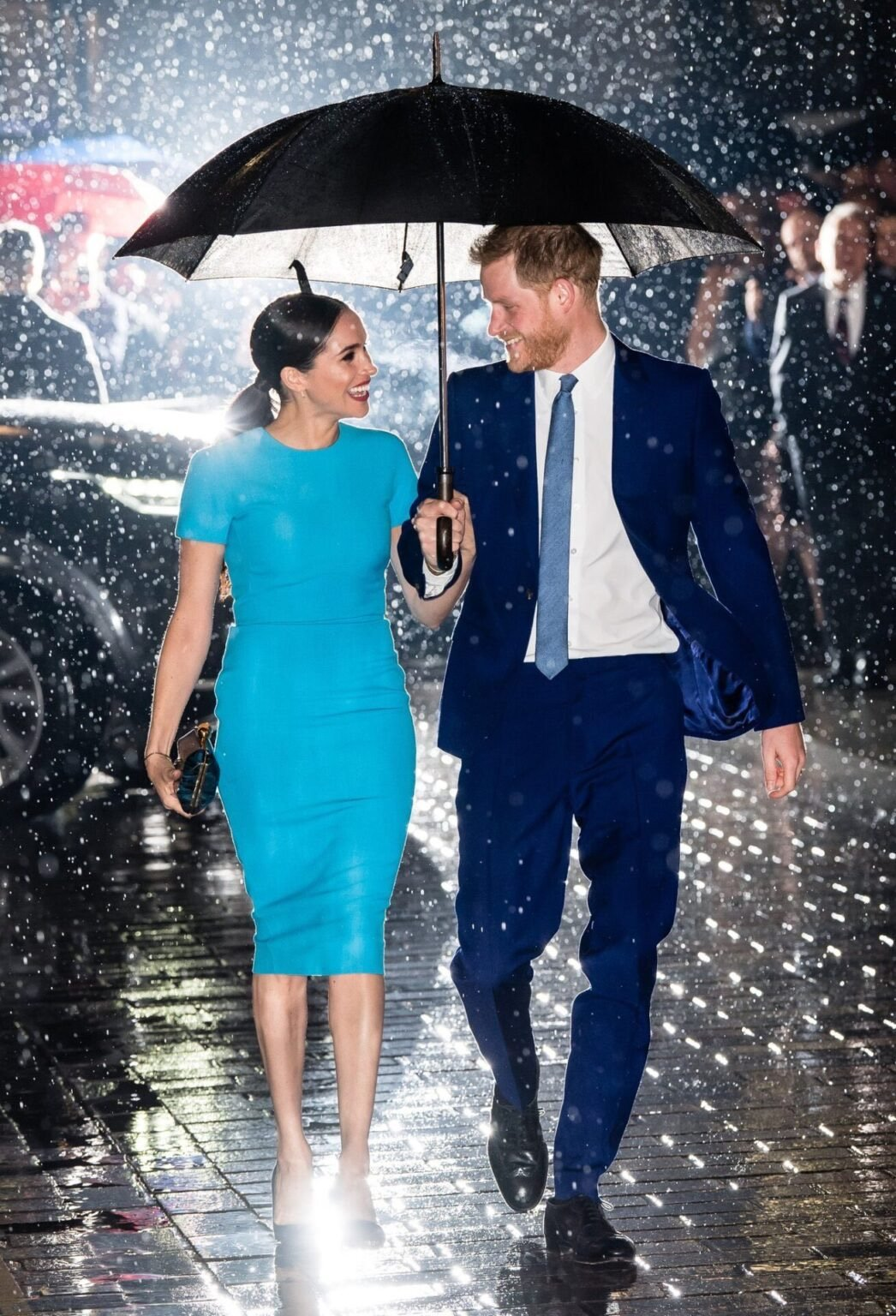 Duchess of Sussex Meghan Markle smiles at Prince Harry under an umbrella wearing bright turquoise colored Victoria Beckham dress