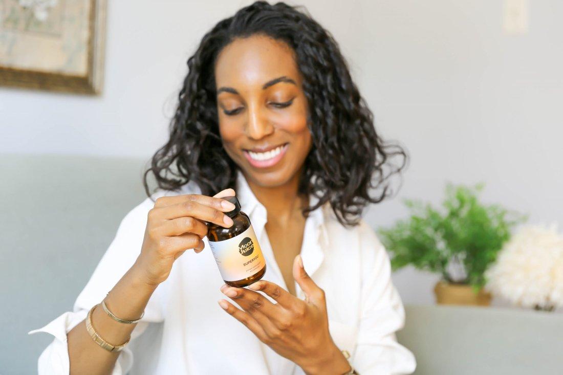 Lana Jackson holds Moon Juice SuperYou supplements jar