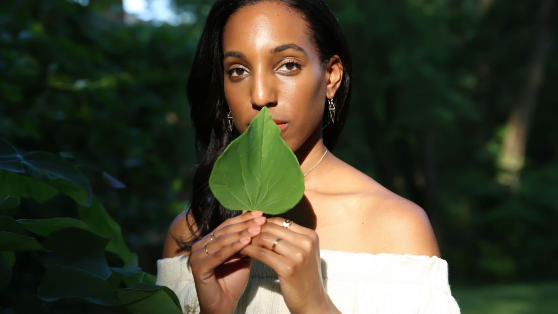 Lana Jackson posing in sunlight with green leaf up to her mouth wearing Peggy Li Creations Chain Rings