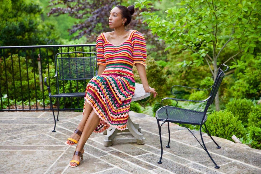 Lana Jackson leans against stone table in a garden patio wearing Farm Rio Crochet Midi Dress