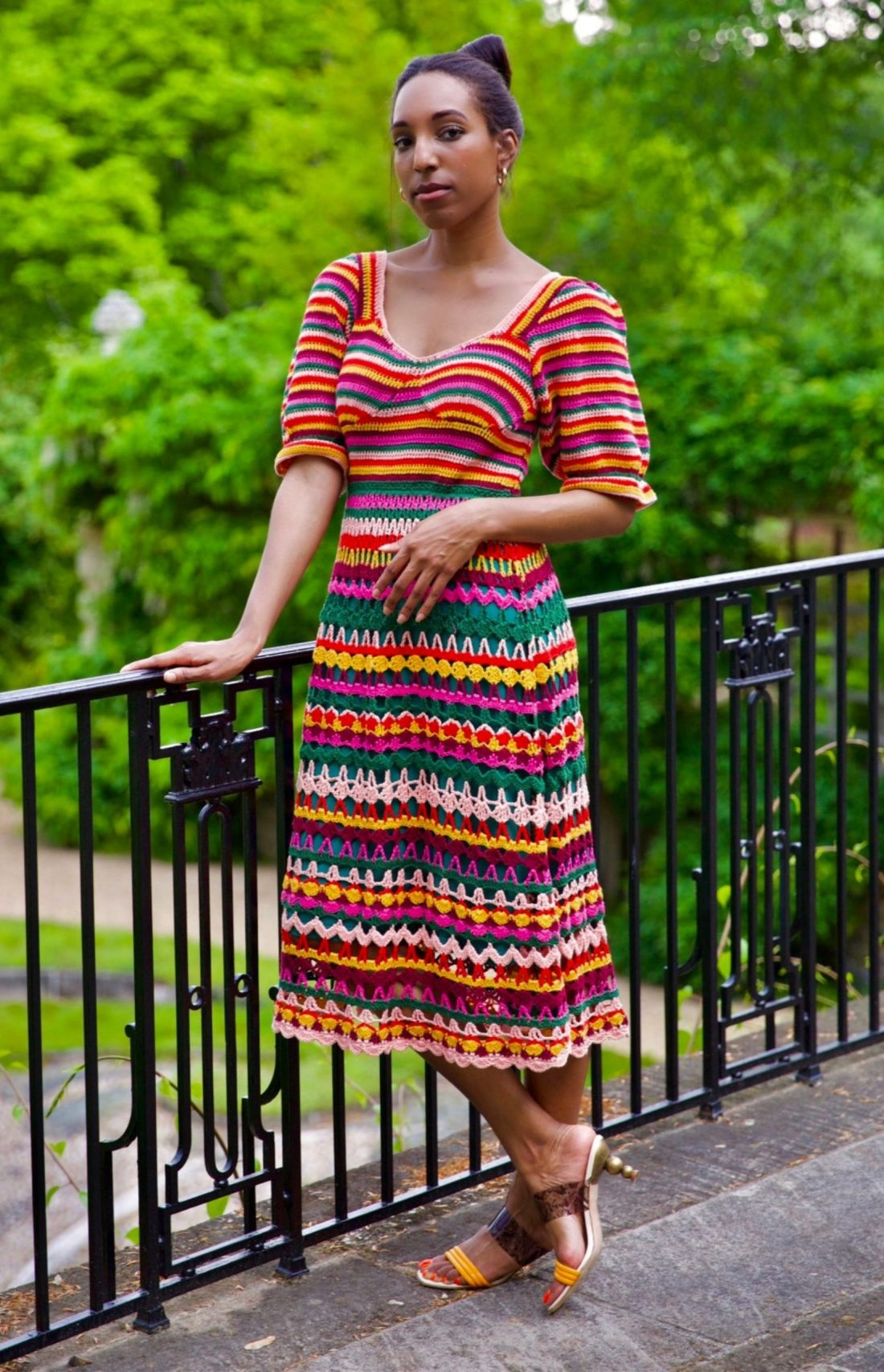 Lana Jackson stands posing against garden patio railing wearing Farm Rio Crochet Midi Dress