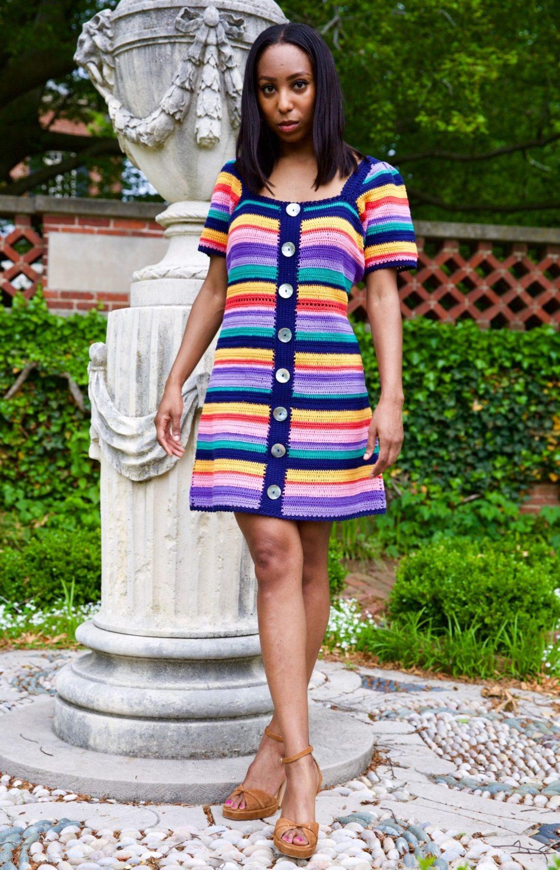 Jilene Jackson stand posing against stone statue in garden patio wearing Farm Rio Rainbow Crochet Mini Dress