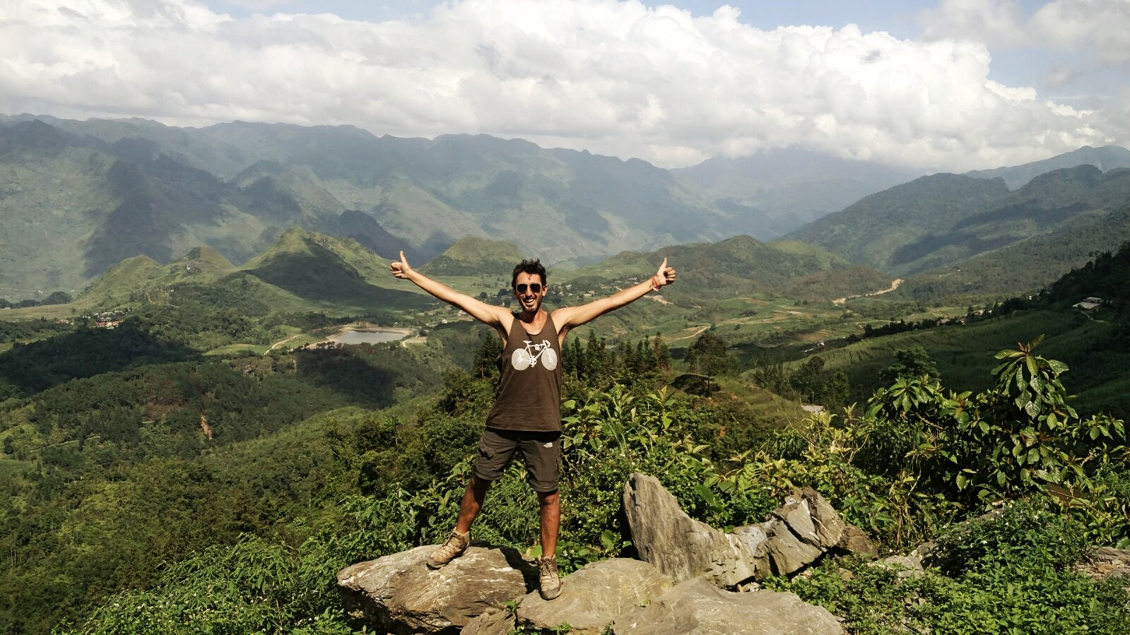 Cristian looking happy and staying with his arms outstretched with the mountains background