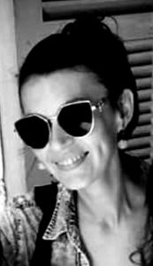The girl wearing sunglasses and smiling
