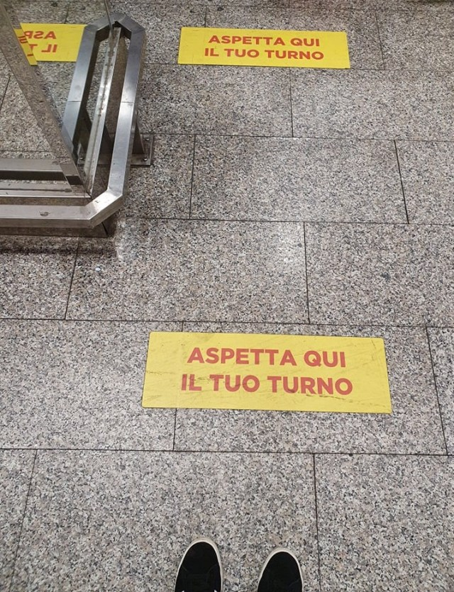 a yellow stop sign in Italian in the supermarket grey floor