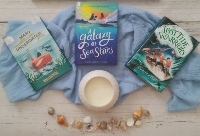 Three books on a scarf with shells and candle.