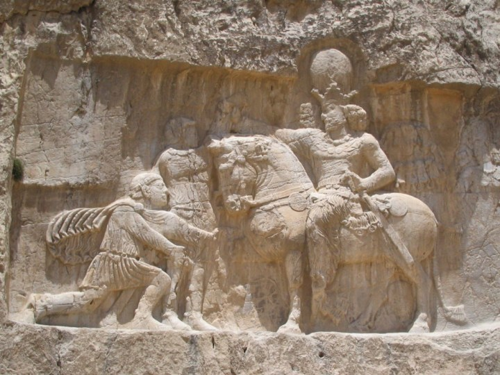 Rock-face relief at Naqsh-e Rustam of Sasnian emperor Shapur I (on horseback) capturing Roman emperor Valerian (standing) and Philip the Arab (kneeling), suing for peace, following the victory at Edessa.