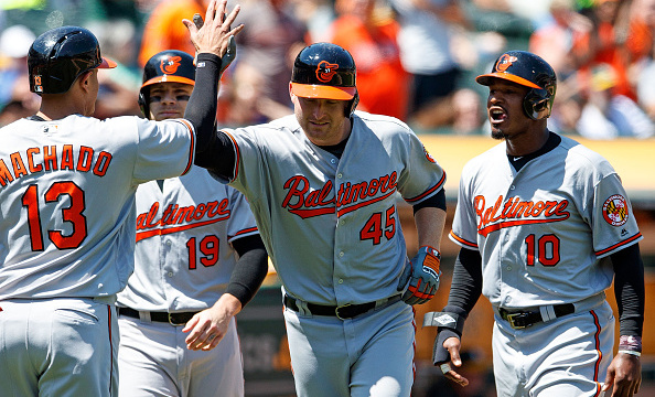 OAKLAND, CA - AUGUST 11: Mark Trumbo #45 of the Baltimore Orioles is congratulated by Manny Machado #13, Chris Davis #19, and Adam Jones #10 after hitting a grand slam home run against the Oakland Athletics during the fifth inning at the Oakland Coliseum on August 11, 2016 in Oakland, California. The Baltimore Orioles defeated the Oakland Athletics 9-6. (Photo by Jason O. Watson/Getty Images)