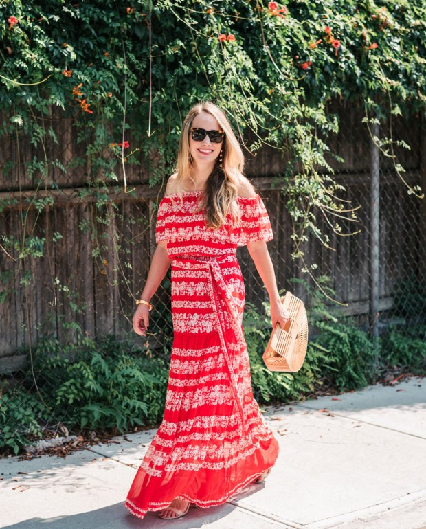 spray tan tips for an even tan like this girl in a red dress and shades with a fence and green leaves in the background