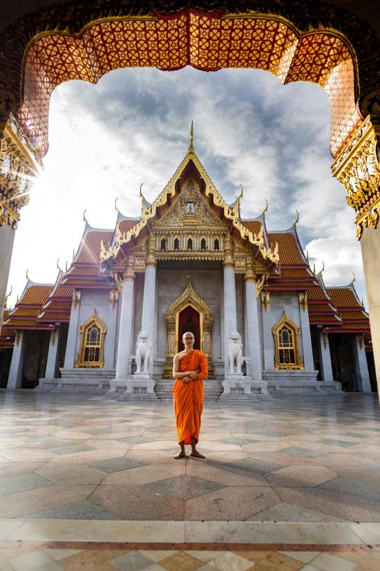 monk-standing-in-front-of-temple-3393546