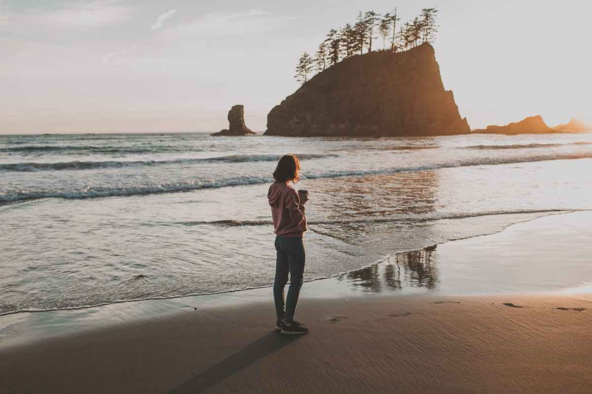 photo of woman standing on seashore during sunset