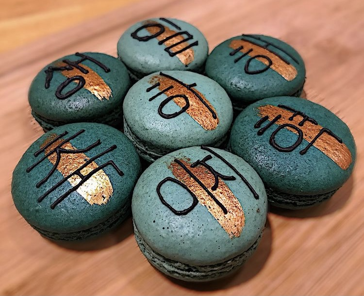 In this image, a collection of Korean macarons that Arisa has made are on display. They range in a variety of blue shades, with Korean words on top and a gold line underneath the writing.