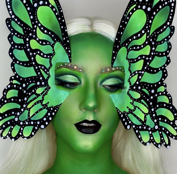 In this image, Niamh has painted her whole face green, with glittered eyebrows and black lipstick. On each side of her face are green and black wings, to look like butterfly wings. She is wearing a white wig.