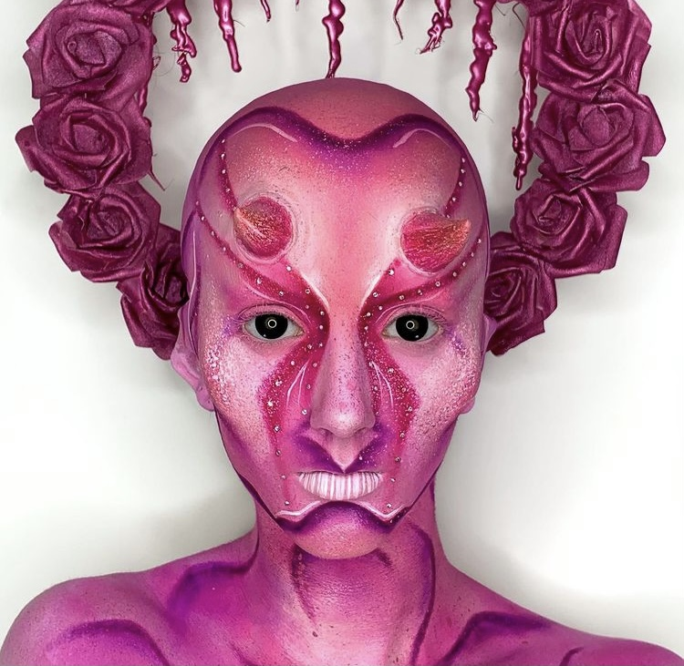 In this image, Niamh has painted her face, neck and shulders hues of purple and pink. There are darker lines to contour and create structure. She is wearing pink horns on her head. She is also wearing a halo of pink/purple roses.