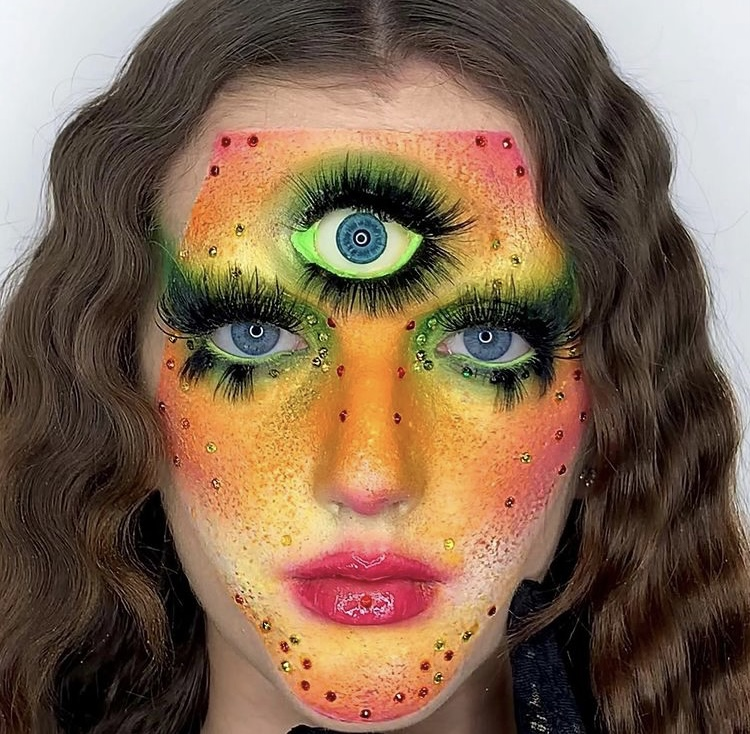 In this image, Niamh has painted her face shades of orange, yellow, red and green. She has also used makeup to create a third eye on her forehead.