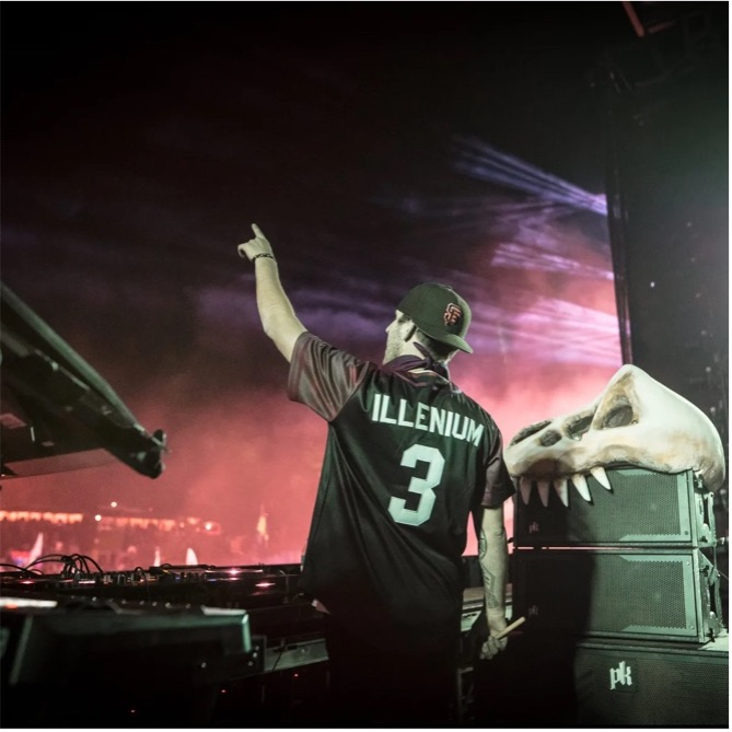 """In this image, Illenium is wearing a top that says: """"Illenium 3"""" on the back. He is stood behind his DJ-ing desks on stage whilst raising his arm in the air towards the audience."""