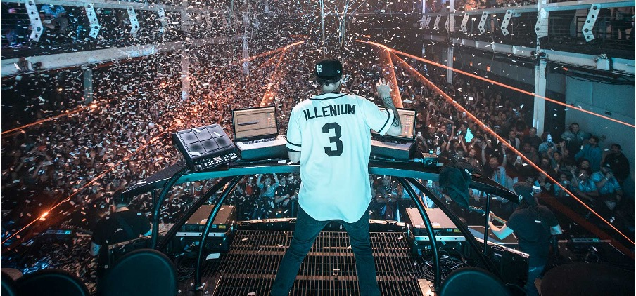 In this image, Illenium is stood behind his DJ-ing desks on stage with a crowd in front of him.