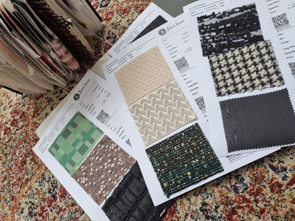 In this image, there are multiple types of fabrics stuck to paper. They are all cut into equal squares. Ravina may have been testing different fabrics for her designs.