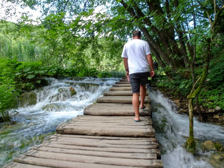 Man walking on wooden path over a waterfall.