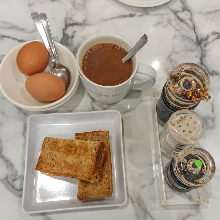 Kaya toast set - includes toast, kopi, two half-boiled eggs in a bowl, and a tray of condiments
