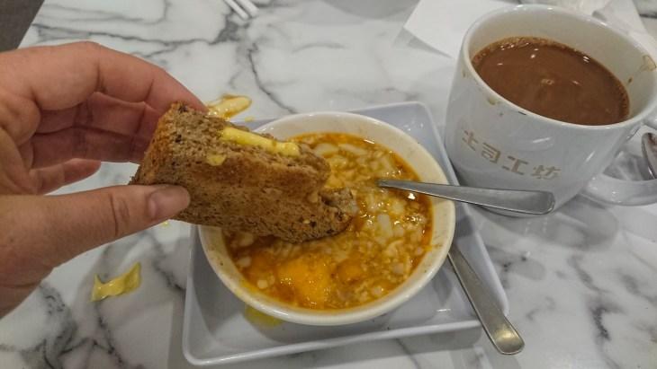 Hand dipping Kaya toast into half-boiled egg dish
