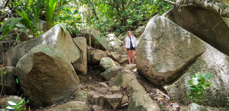 Keelie standing on a hiking trail with large boulders.