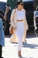 Kim K rocks a white co-ord and pink duster jacket