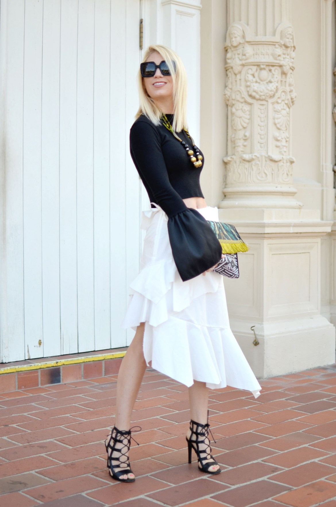 Stefanie of the Style Safari wears storets feel the vibes frayed white skirt, cropped pixie market black top, handmade african clutch and necklace