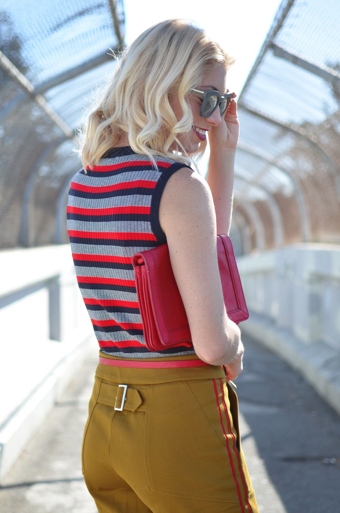 Stefanie of The Style Safari wears a military casual outfit with striped knit tank and pops of red heels and clutch
