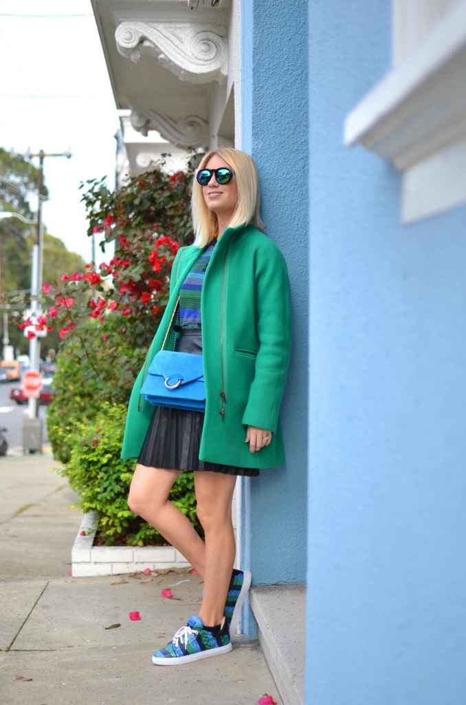 emerald green and bright blue outfit, kelly green coat, pleated faux leather black skirt, blue suede shoulder bag, snakeskin sneakers // thestylesafari.com