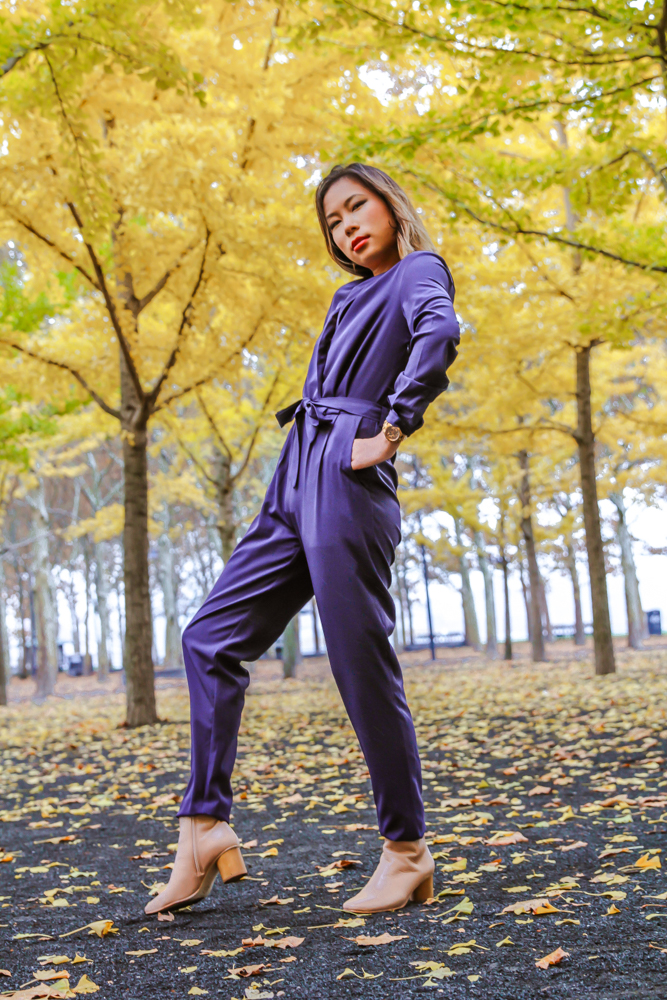 kasey ma of thestylewright wearing blue jumpsuit posing in park with trees