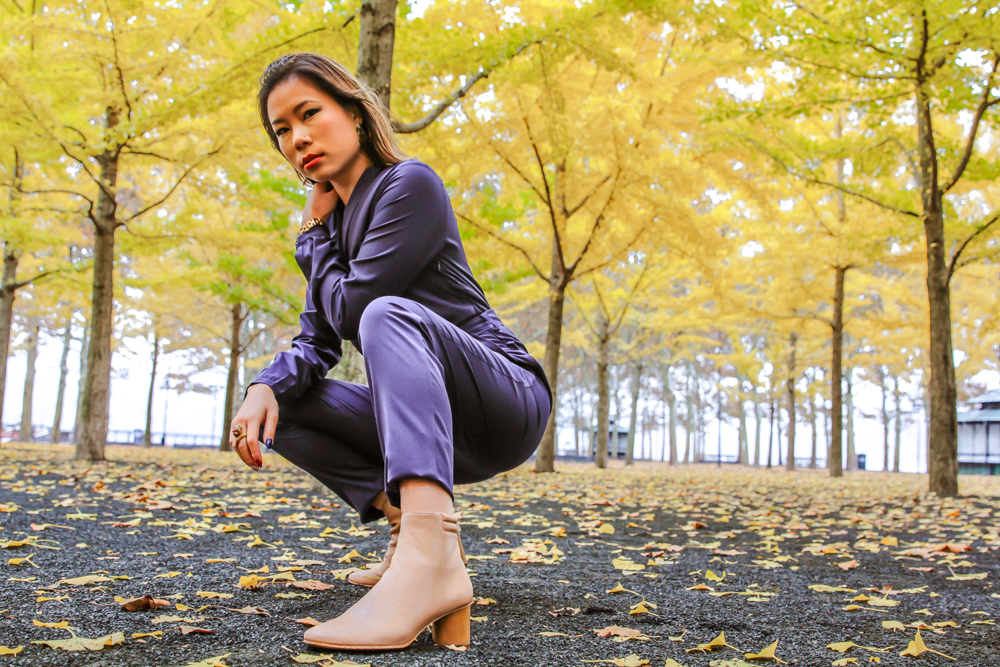 kasey ma of thestylewright wearing blue jumpsuit posing in park with trees crouched down