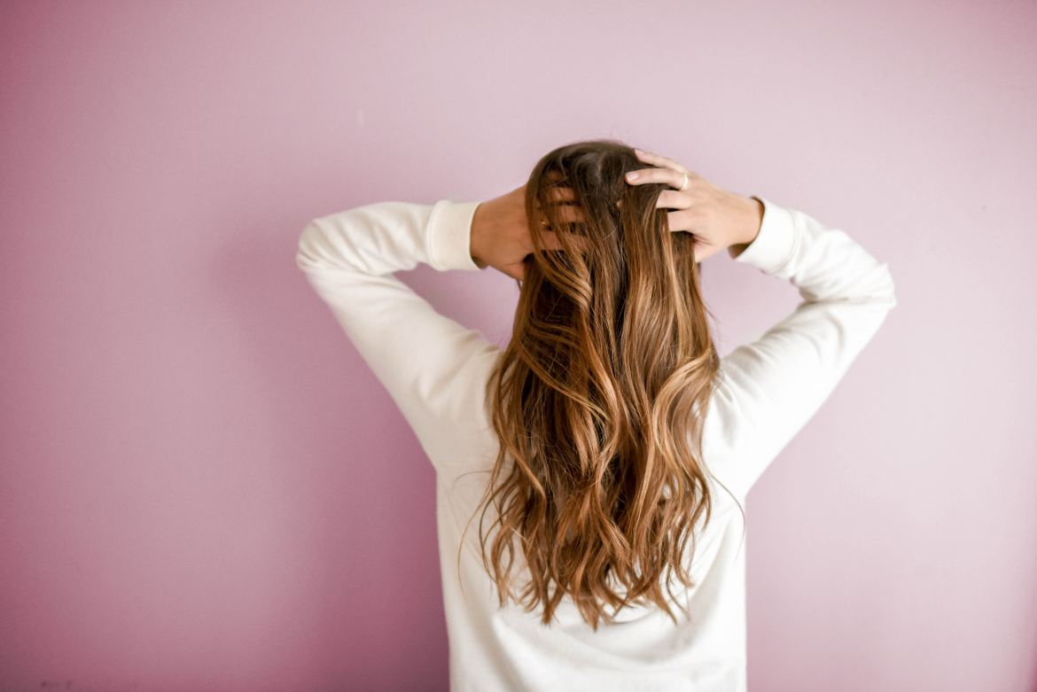 woman hands on head facing pink wall