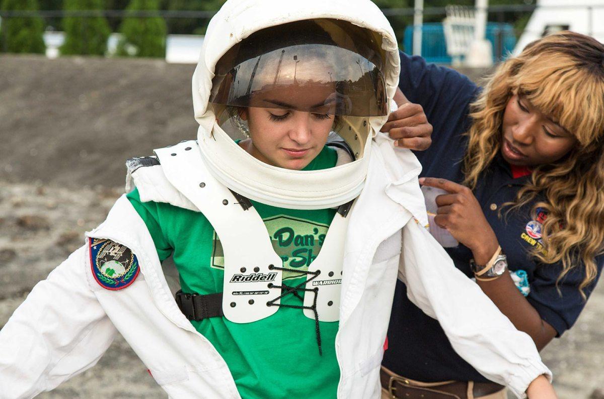 L'allenatrice di equipaggi Latina Rivers aiuta Amber, 16 anni, di Pittsburgh, a vestirsi per camminare su una superficie lunare simulata durante uno Space camp a Huntsville, Usa.