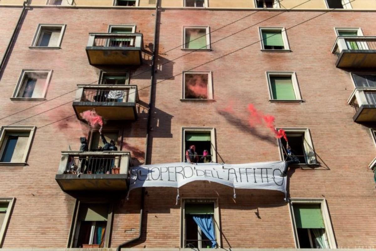 fumogeni rossi si sollevano dalle finestre di una palazzina, uno striscione legge Sciopero dell'affitto