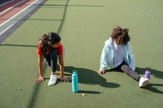 black girl doing split while friend stretching before training on stadium