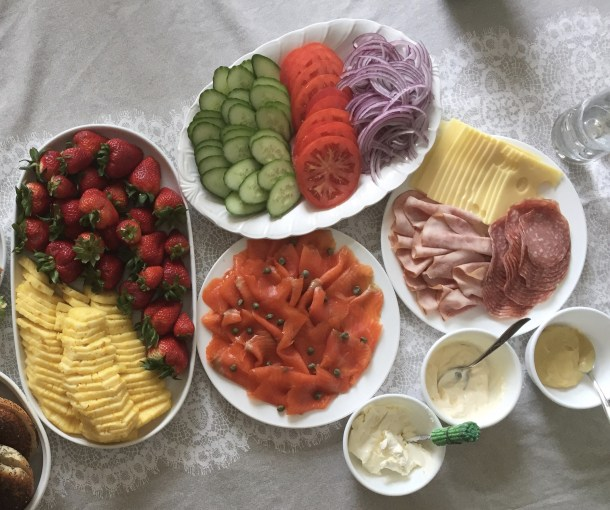 platter of cold cuts, smoked salmon, sandwich toppings, and fruit platter on table