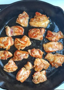 pieces of browned chicken in cast iron skillet