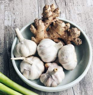 ginger and garlic in a bowl with green onions on the side