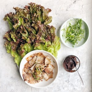 lettuce wraps and pork belly on platter with bowl of ssam sauce on side