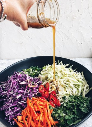 asian slaw with hand pouring dressing into bowl