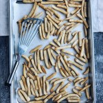 sheet pan of french fries with spatula
