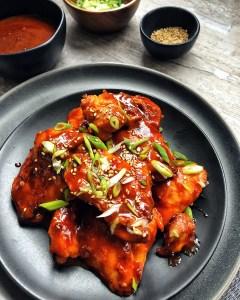 gochujang chicken piled onto black plate