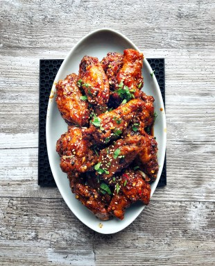 oval platter of Korean fried chicken on wood background