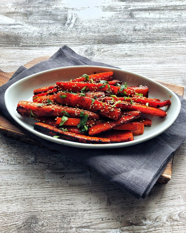 Gochujang Roasted Carrots on oval platter, with napkin and cutting board underneath