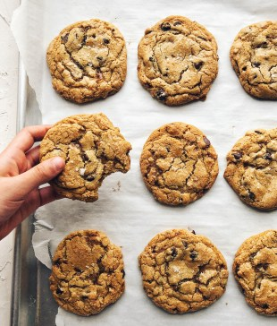 cookies on a sheet pan, with a hand holding one