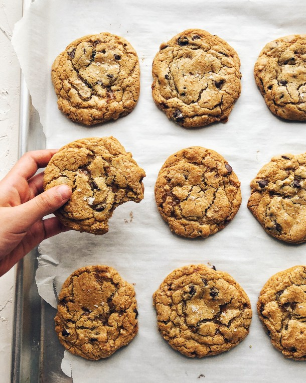 cookies on a sheet pan with hand holding one cookie