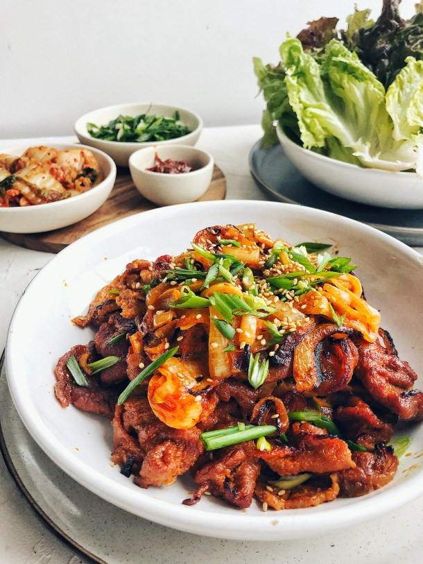Korean spicy pork mounded in bowl with lettuce wraps and kimchi on the side